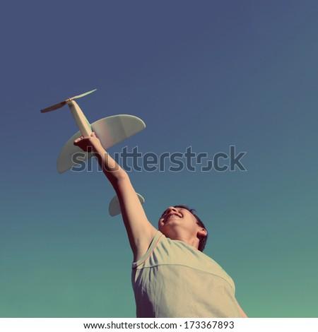 happy boy running airplane model - vintage retro style - stock photo
