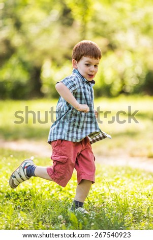Happy boy running in park - stock photo
