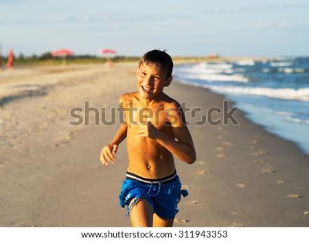 Happy boy running on the sea beach at summer. - stock photo