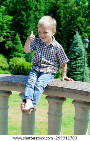 Happy boy showing sign okay with fingers. He with blond hair in trendy shirt and jeans, the sitting in the park . Hipster style. Sunny weather. Outdoor shot - stock photo