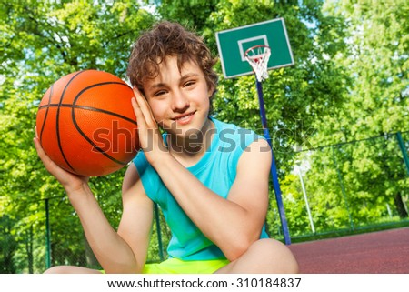 Happy boy sits on playground, holds ball near face - stock photo