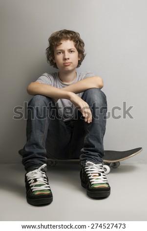 happy boy sitting on skateboard - stock photo