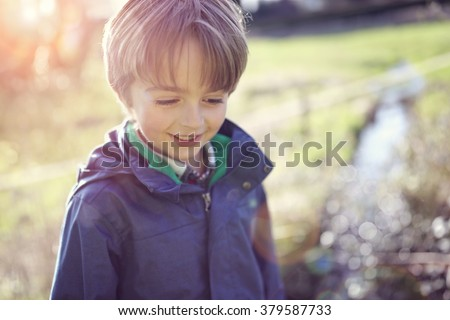 Happy boy smiling in the spring sunshine hiking near a stream - stock photo
