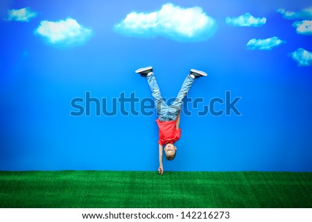 Happy boy standing on his head over blue sky in a bright summer day. - stock photo