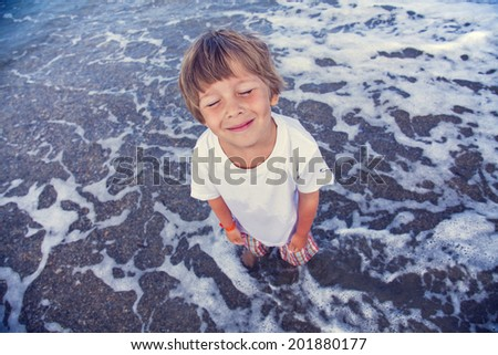 Happy boy swimming and standing in the sea water - stock photo