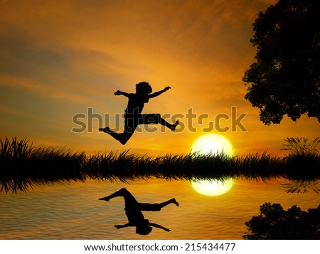 Happy boy, teenager jumping in water, over lake with sunset background, body reflection in water. Outdoor exciting summer vacation, travel life, leisure. Lifestyle freedom concept - stock photo