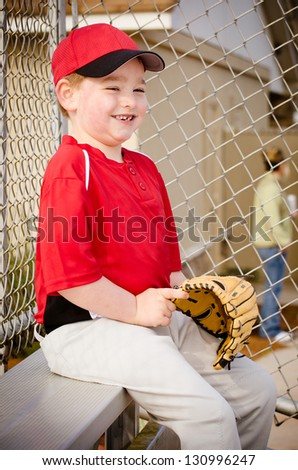 Happy boy waiting for start of his baseball game - stock photo