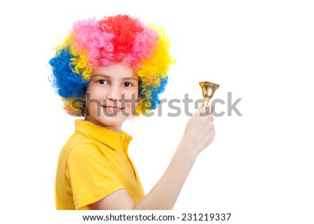 Happy boy wears colorful wig and calls by hand bell - stock photo