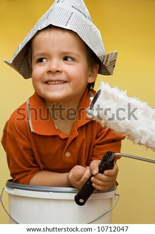 Happy boy with a newspaper helmet, preparing to paint - stock photo