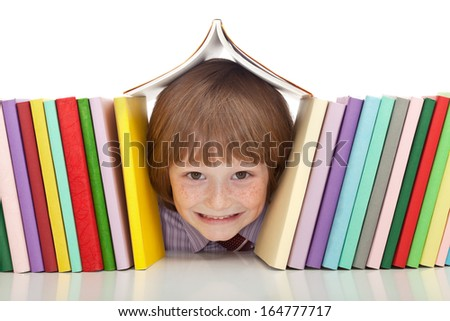 Happy boy with colorful books and a big grin - isolated - stock photo
