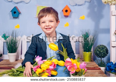 Happy boy with flowers. Yellow and pink tulips,  - stock photo
