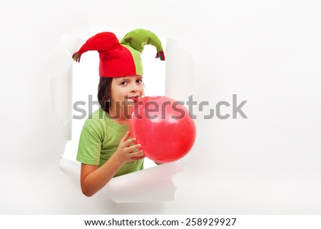 Happy boy with funny hat celebrating with a balloon - peaking through a torn hole in paper - stock photo