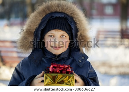Happy boy with gift box outdoors - stock photo