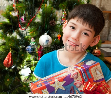 Happy boy with gifts in front of Christmas tree. - stock photo