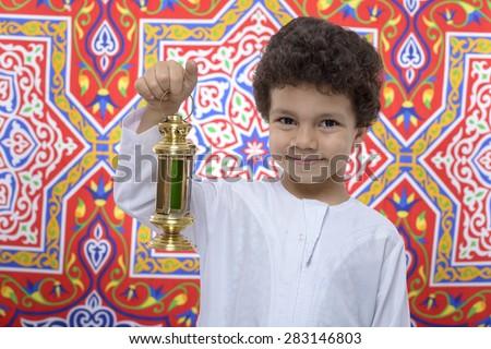 Happy Boy with Golden Lantern Celebrating Ramadan over Ramadan Fabric - stock photo