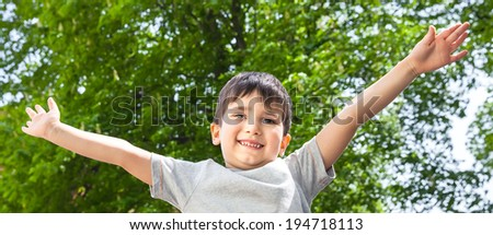 Happy boy with his hands up smiling on green tree background - stock photo