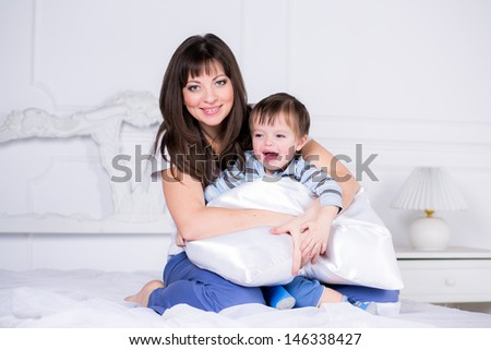 happy boy with his mom on the bed in his pajamas - stock photo