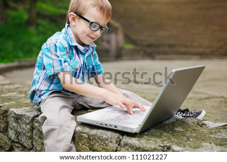 Happy boy with laptop - stock photo