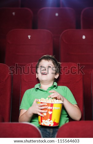 Happy boy with popcorn watching a movie - stock photo