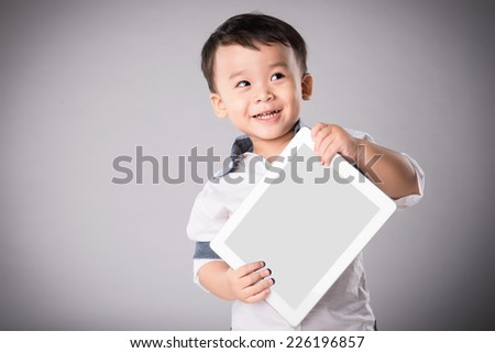 Happy boy with tablet computer. Child showing tablet. Little asian boy smiles with tablet computer on isolated background - stock photo