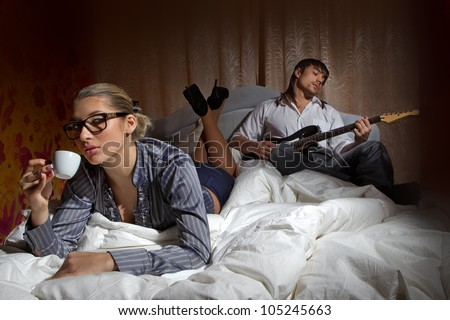 Happy boyfriend with electric guitar - playing and woman drinking coffee with pleasure on bed - stock photo