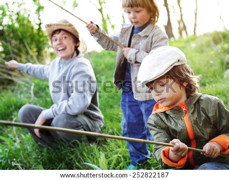 happy boys go fishing on the river - stock photo
