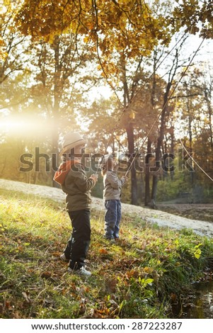 happy boys go fishing on the river, photo with artistic lens flare - stock photo