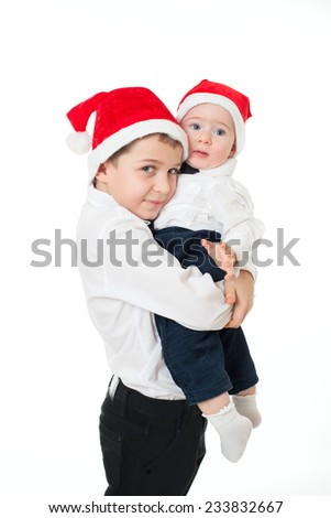 Happy boys kids brothers friends in santa's hats isolated on white, major brother holding hugging the junior - stock photo
