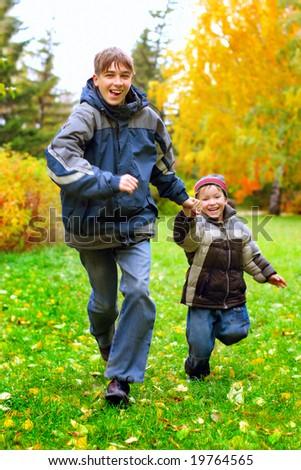 happy boys runing in the autumn park - stock photo