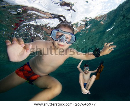 Happy boys  snorkeling in a sea - stock photo