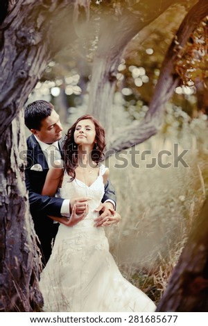 Happy bridal couple in forest. Summer wedding picture. - stock photo