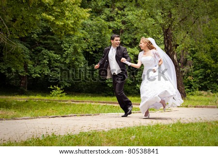 happy bride and bridegroom running along the alley in the park - stock photo