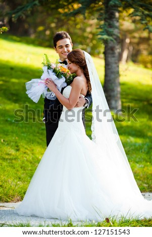 happy bride and groom at a park on their wedding day - stock photo