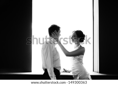 Happy bride and groom at the wedding walk in front window - stock photo