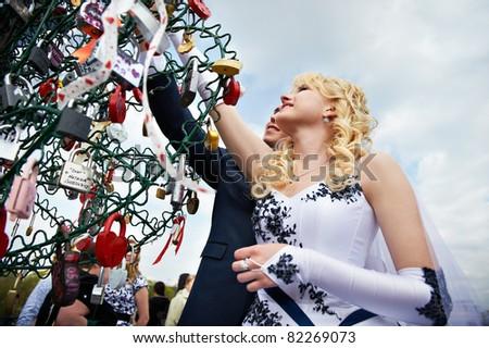 Happy bride and groom at wedding walk on Luzhkov bridge in Moscow - stock photo