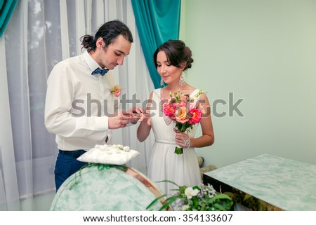 Happy bride and groom exchange rings at the wedding ceremony - stock photo