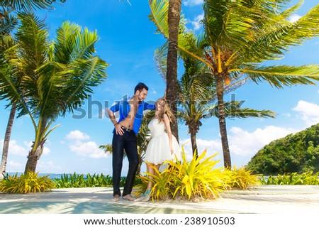 happy bride and groom having fun on a tropical beach - stock photo