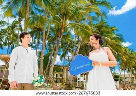 Happy bride and groom having fun on a tropical beach under the palm trees. Wedding and honeymoon summer vacation concept. - stock photo
