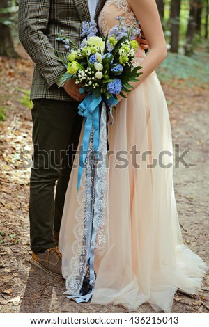 happy bride and groom holding bouquet in the summer wood. Just married loving hipster couple in wedding dress and suit in green forest at sunset. Romantic Married young family in the park - stock photo