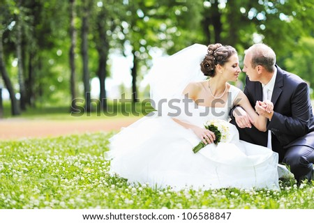 Happy bride and groom in a park. Wedding couple - stock photo