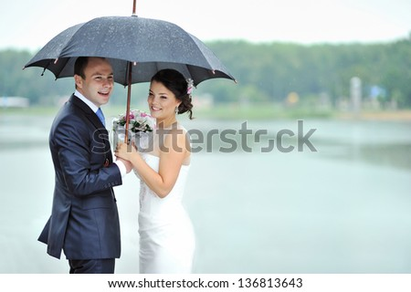 Happy bride and groom in a rainy wedding day hiding from rain - stock photo
