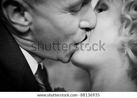 Happy bride and groom kissing. Black and white - stock photo