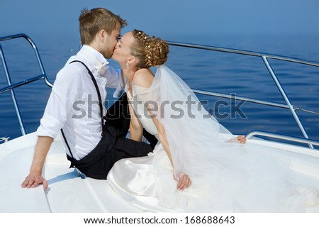 Happy bride and groom kissing on a yacht - stock photo