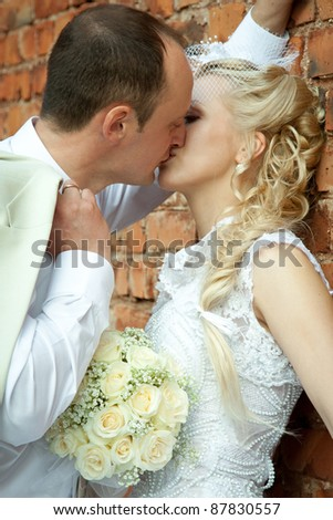 Happy bride and groom kissing; wedding day - stock photo