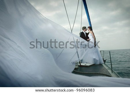 Happy bride and groom on a yacht - stock photo
