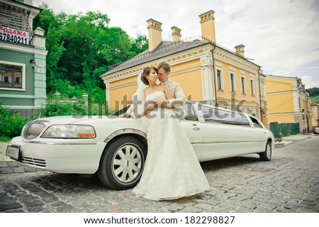 happy bride and groom on the background of a limo - stock photo