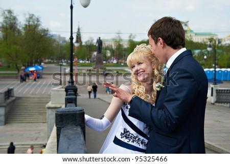 Happy bride and groom on wedding walk in city park - stock photo
