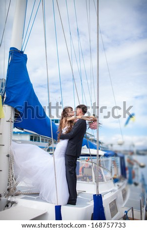Happy bride and groom on yacht at wedding day. Newlywed couple outdoors near sea. - stock photo