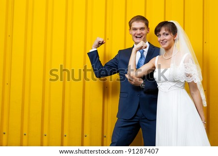 Happy Bride and groom posing against yellow wall - stock photo