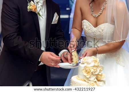 happy bride and groom tasting luxury wedding cake decorated with roses at reception, catering in restaurant - stock photo